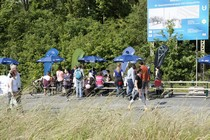 Some tables, benches and umbrellas with some people standing around them. There is grass in the foreground.