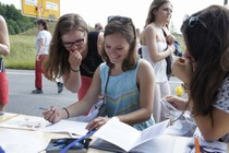A girl writing something on a sheet. A second girl is looking over her shoulder and stifling a laugh.